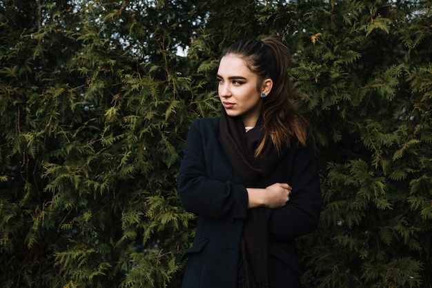 Stylish young woman in coat with scarf near coniferous plants