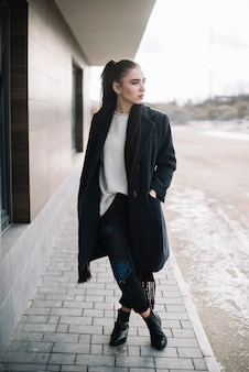 Stylish young woman in coat with scarf on street
