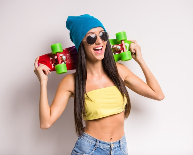 Stylish young woman in colorful clothes with skateboard.