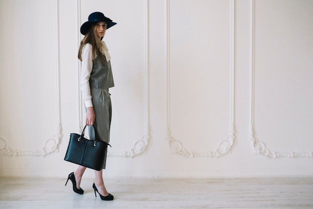Stylish young woman in costume and hat with handbag in room