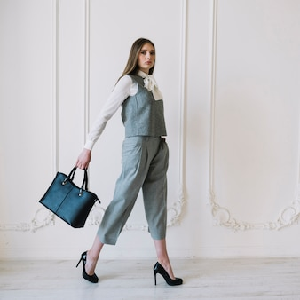 Stylish young woman in costume with handbag in room