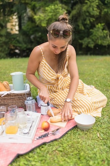 Stylish young woman cutting bread with knife at picnic