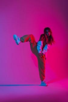 패션 운동화에 트렌디한 스포츠 청소년 옷을 입은 세련된 젊은 여성 댄서는 밝은 분홍색 빛으로 스튜디오의 한쪽 다리에 서 있습니다. 다양한 색상의 네온 컬러로 방에서 춤을 추는 현대적인 소녀.