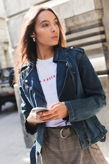 Stylish young woman in denim jacket using smartphone