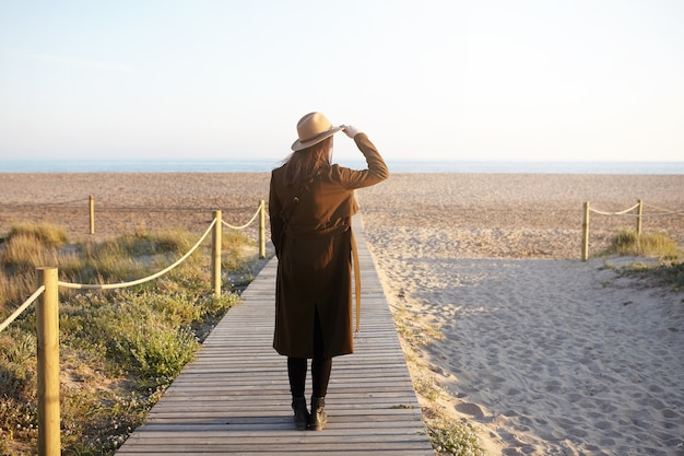 Stylish young woman dressed in warm coat, holding brim of her trendy felt hat because of wind