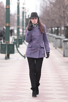 Stylish young woman in hat and autumn coat walking along the city