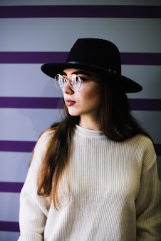 Stylish young woman in hat and eyeglasses