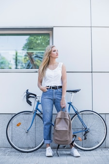 Stylish young woman holding backpack standing against bicycle