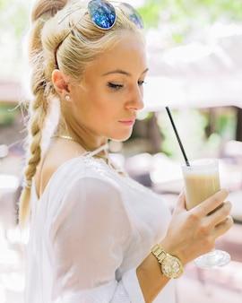 Stylish young woman holding glass of latte macchiato
