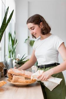 Стильная молодая женщина, держащая органический хлеб