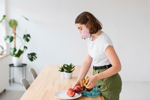 Giovane donna alla moda che tiene frutta organica