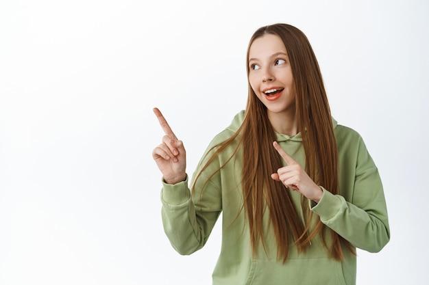 Elegante giovane donna in felpa con cappuccio, guarda da parte e indica il logo, mostra la strada, dimostra il banner del prodotto, in piedi sul muro bianco