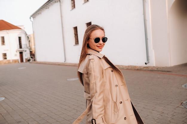 ベージュのコートと黒い帽子を手に、街の通りで眼鏡をかけたスタイリッシュな若い女性