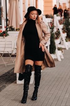 ベージュのコートと黒い帽子をかぶったスタイリッシュな若い女性と街の通りに黒い財布