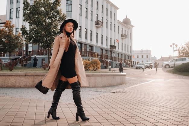 街の通りに黒い帽子をかぶったベージュのコートを着たスタイリッシュな若い女性。女性のストリートファッション。秋の服。アーバンスタイル。
