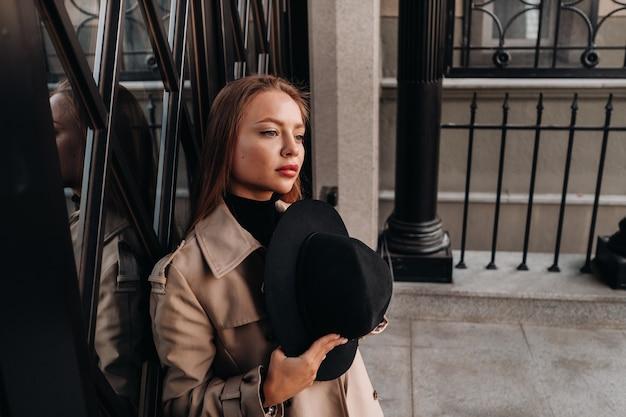 도시 거리에 검은 모자에 베이지 색 코트에 세련 된 젊은 여자. 여성의 스트리트 패션. 가을 의류. 도시 스타일.