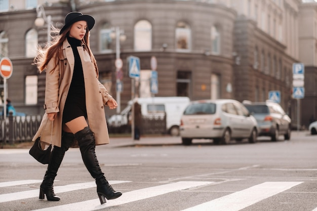 Стильная молодая женщина в бежевом пальто в черной шляпе на городской улице. женская уличная мода. осенняя одежда. городской стиль.