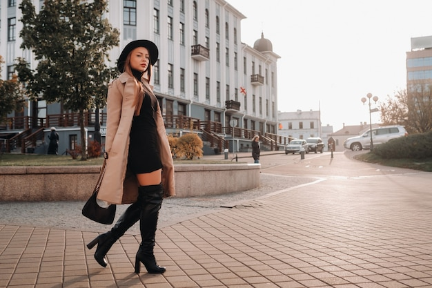 街の通りに黒い帽子をかぶったベージュのコートを着たスタイリッシュな若い女性。女性のストリートファッション。