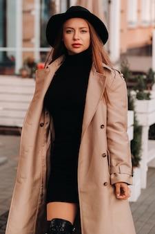 街の通りに黒い帽子をかぶったベージュのコートを着たスタイリッシュな若い女性