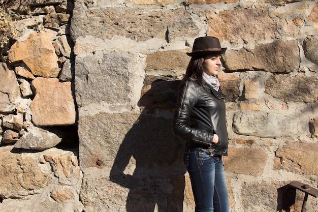Стильная молодая женщина в черной кожаной куртке, модной шляпе и шарфе стоит боком у старой каменной стены на солнце с тенью