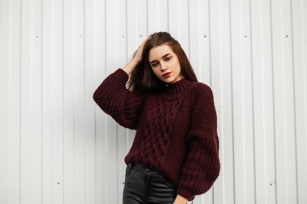 Стильная молодая женщина в бордовом свитере позирует в городе у белой стены