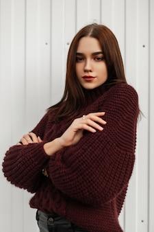 白い壁の近くの街でポーズをとってブルゴーニュのセーターのスタイリッシュな若い女性
