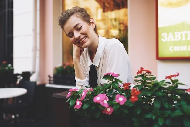 夏にカフェのテーブルに座って本を手にシャツを着たスタイリッシュな若い女性