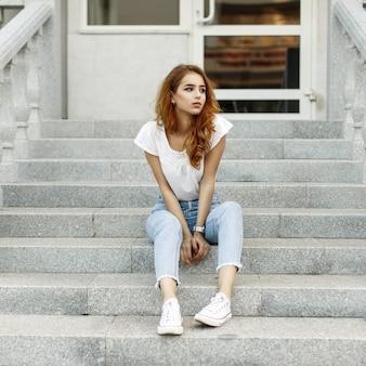 階段に座っている白いシャツ、ジーンズ、スニーカーのスタイリッシュな若い女性。