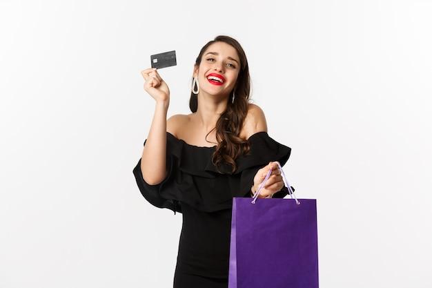 Стильная молодая женщина в черном платье идет по магазинам, держа сумку и кредитную карту, улыбаясь довольна, стоя на белом фоне.