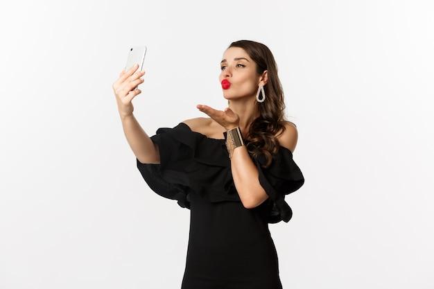 Стильная молодая женщина в черном платье, вечеринки и селфи на мобильном телефоне, отправка воздушного поцелуя на камеру смартфона, стоя на белом фоне.