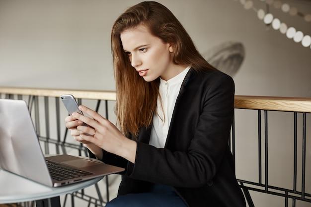 携帯電話を使用してノートパソコンの画面の写真を撮るカフェでスタイリッシュな若い女性