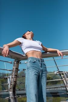 Стильная молодая женщина в повседневном белом топе и джинсах позирует на городском мосту в солнечный жаркий день