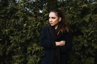 Стильная молодая женщина в пальто с шарфом возле хвойных растений