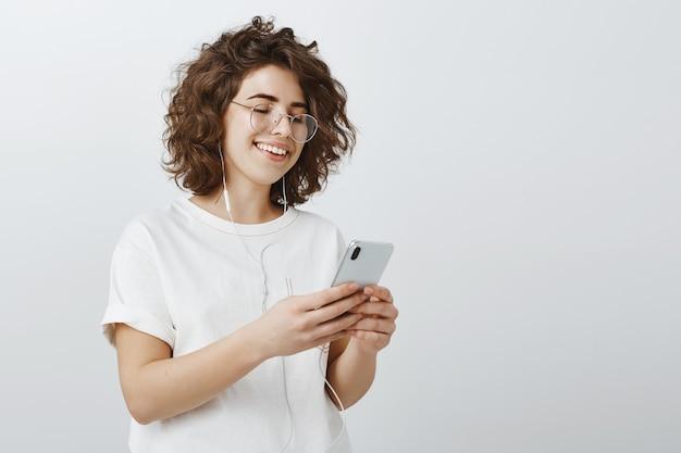 Стильная молодая женщина в очках делает плейлист в телефоне, слушает музыку через наушники