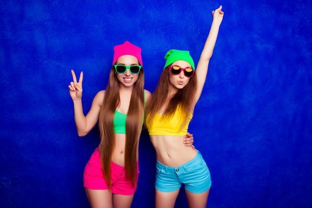 彼女の妹が2本の指で身振りで示す間、ふくれっ面の眼鏡をかけたスタイリッシュな若い女性