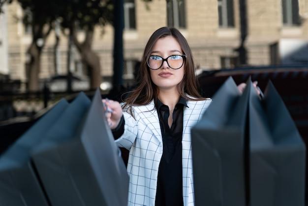 Стильная молодая женщина в очках с черными сумками после успешных покупок. девушка-шопоголик. черная пятница, распродажа, скидки.