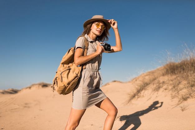카키색 드레스에 세련된 젊은 여성이 사막 모래에서 걷고, 사파리에서 아프리카를 여행하고, 모자와 배낭을 착용하고, 빈티지 카메라에 사진을 찍습니다.