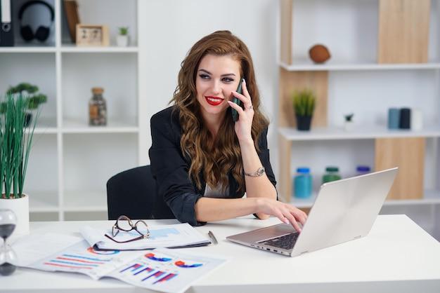 公式の服を着たスタイリッシュな若い女性は、彼女のオフィスでビジネスパートナーとモバイル会話をしています。