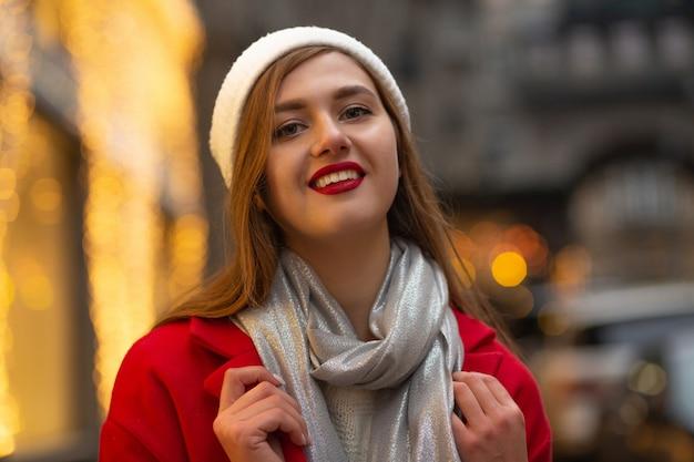 ストリートフェアで歩く赤いコートのスタイリッシュな若い女性