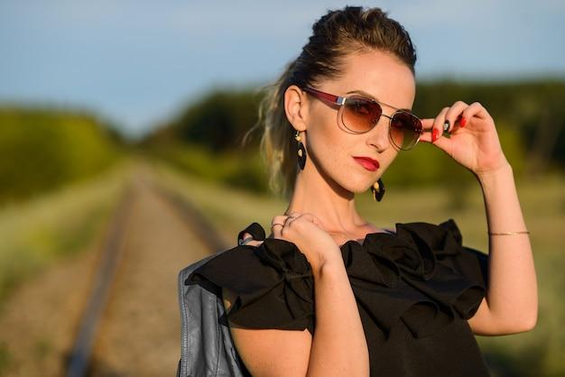 자연의 배경으로 포즈를 취하는 선글라스에 세련 된 젊은 여자. 복사 공간 주근깨가 여자의 초상화입니다.