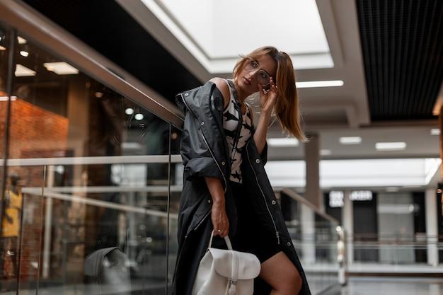 쇼핑몰에서 쉬고 흰색 가죽 배낭 패턴으로 유행 티셔츠에 유행 재킷에 빈티지 안경에 세련 된 젊은 여자. 유행 소녀 모델. 미국식.