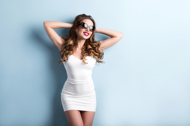 水色の壁の背景にスタイリッシュな若い女性が幸せです。