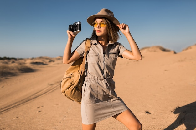 Stylish young woman in khaki dress walking in desert, traveling in africa on safari, wearing hat and backpack, taking photo on vintage camera