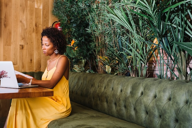 Stylish young woman looking at documents with laptop on wooden table in the restaurant