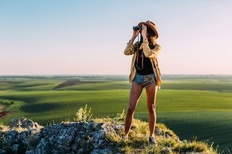 Stylish young woman looking through binoculars