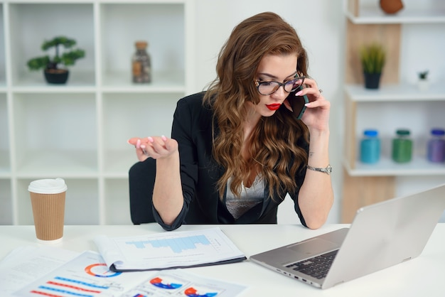Stylish young woman in official clothes has mobile conversation with business partner in her office.