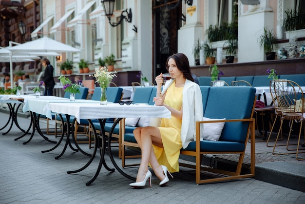 도시 거리 카페 테라스에서 커피를 마시는 세련된 젊은 여성 또는 10대 소녀. 노란 드레스와 흰색 재킷을 입은 소녀.