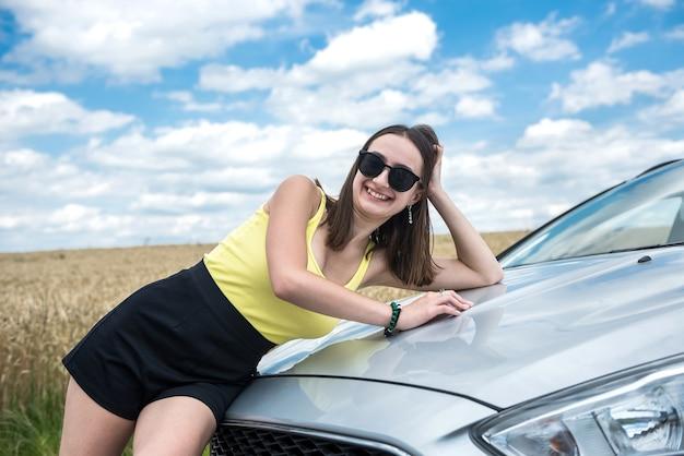세련된 젊은 여성이 여행을 일시 중지하고 차 근처의 길가에 달려 있습니다.