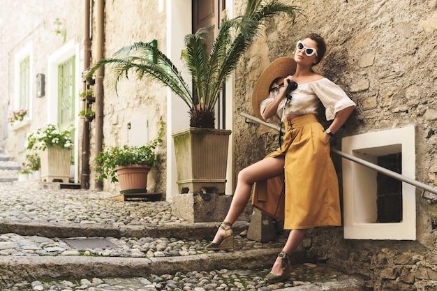 イタリアの小さな町の通りでポーズをとるスタイリッシュな若い女性
