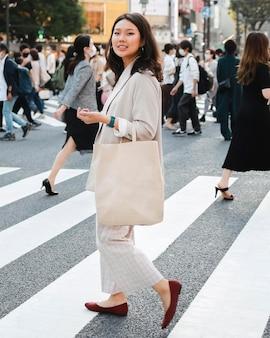 Una giovane donna alla moda che propone sulla strada